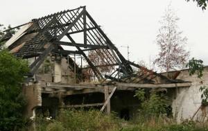 De uitgebrande boerderij ligt er al acht jaar onveranderd bij.